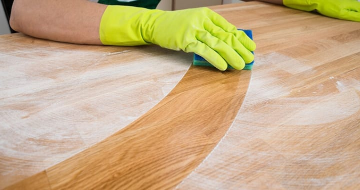 Person wearing rubber gloves cleaning a dirty wooden work surface with a sponge