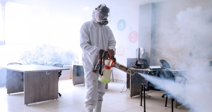 Employee wearing PPE carrying out disinfectant fogging